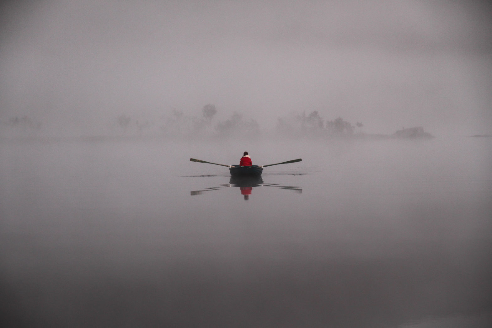 Person i båt, alene på tåkete vann.