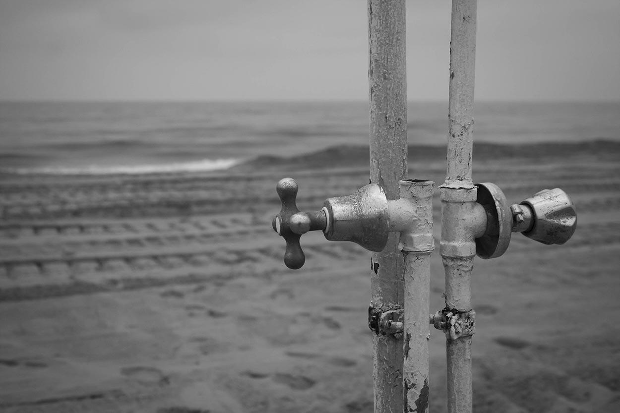 Dusjkran på ei øde strand.